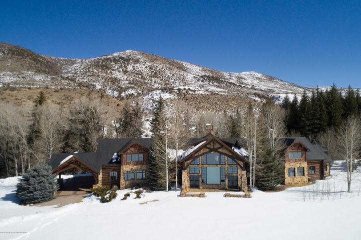 With unparalleled views in nearly every direction, The Ranch at Snowmass Creek embodies the ultimate Colorado experience. The property consists of three main structures with a private pond, three fenced horse paddocks and a training corral, sitting on a tract of land covering both sides of pristine Snowmass Creek with a post and beam bridge across the river.The primary residence consists of approximately 8,500sqft of living space, a finished enclosed gazebo with hot tub, and finished two car garage. The exterior of the  residence has a spacious, well lit Porte Cochere at the entrance and two spacious flagstone patios; one on the east side with an outdoor fireplace overlooking Snowmass Creek and one on the west side of the house looking directly at Mount Sopris.