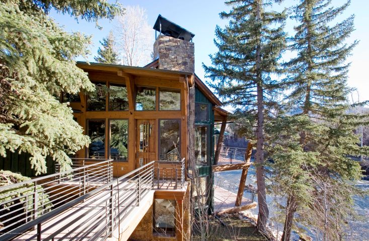 RiveRoar sits directly on the bank of the Roaring Fork River where no new Pitkin County home can be built today. Current code requires a 100-foot setback.  Resembling a glass treehouse, the home appears to have been dropped by helicopter into a stand of more than twenty 75-foot evergreen trees and offers views from every room.  It has wonderful outdoor spaces to truly capture the river life during the day or at night by the fire-pit.  Watch suspended trout in the crystal-clear eddies from the cantilevered dining room window, cleverly designed by David Johnston's award-winning architectural team.  Best river front home in Woody Creek and OId Snowmass