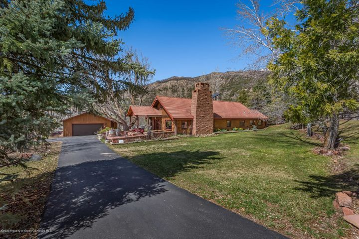 Unique log home in Basalt, a quick walk from the elementary, middle school and downtown. Built 65 years ago as ''The Hunting Lodge of Basalt'' and now sits on almost half an acre. The home has been remodeled to become a family home at 3002 SF with 3 BR/2.5 BA. It has a fabulous stone fireplace, updated kitchen, radiant floor heat and new boiler. Enjoy this beautifully landscaped property adjacent to open space, and has permaculture gardens with orchard. Spacious patios front and back with Hot Tub/BBQ. In addition, it has a heated garage with tool room, solar panels and art studio/workshop area with ample power.