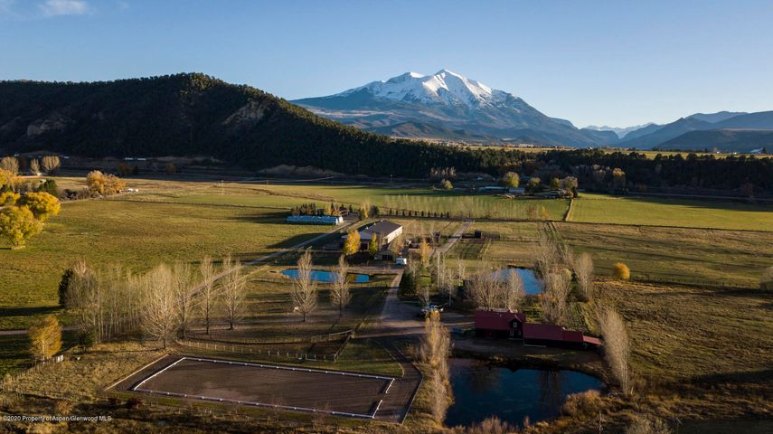 It doesn't get more centrally located than this! Situated with the convenience of downtown Carbondale just a mile away, this unique, private equestrian facility is like nothing offered in the Roaring Fork Valley. Encompassing over 11 acres with extensive water rights and views of Mt. Sopris from the valley floor, this property is perfect for someone looking for a private riding facility or a small commercial riding program. Relax pond side just steps outside your door with Mount Sopris as your backdrop. The three bedroom, 3800sqft home is the perfect combination of mountain and farm living. Rustic log and steel accents give the house a modern yet cozy feel. Use the home as it was designed or expand to add room for extended family and friends. There is also two-bedroom, two bath guest house which can be used as-is or renovated to its full potential. Per Garfield County regulations, the Rural zone district allows maximum lot coverage of 15% with no maximum floor area ratio.  The indoor arena measures at 72'x180' and boasts Martin Collins CLOPF fiber additive into the soil allowing the horse to work on top of the surface reducing strain and allowing freedom of movement. The arena is insulated, lighted, for day or night time use and can easily be heated. The barn also offers viewing windows for natural light. There are 3 additional stalls attached to the arena for guest horses or breeding purposes.  Located privately on the back side of the property, the outdoor arena is 80'x200' with imported sand footing. The arena has been constructed using 4-feet of base layers to optimize draining, allowing the arena to be utilized virtually year-round. There are also 5 sprinkler heads around the perimeter to easily control dust.  The main barn is constructed of nine 12'x12' stalls with Dutch doors opening to sand runs. A tack room and office offer room for daily operations. Five water spigots inside the barn make water transport to stalls effortless. Stall fans along with electric