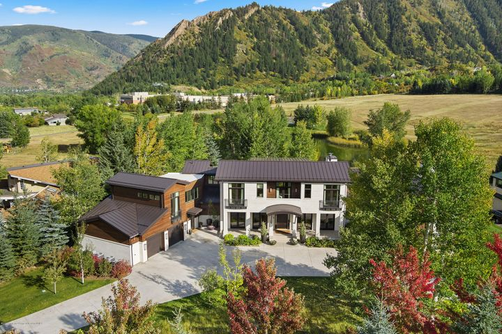 Escape to a designer getaway on 1.19 acres! This David Easton and Rodney Austin masterpiece stuns with unobstructed views of Aspen Mtn, Aspen Highlands, Red Mtn, and Tiehack. An open floor plan of over 9,200 sq. ft. reveals a gracious main living level with a gourmet kitchen, great room and entertainment spaces, ensuring everyone can comfortably spread out. All rooms (except for the gym) are above grade, filling each space with light. Enjoy fabulous outdoor living with gardens, flat lawn, hot tub, fire pit, outdoor kitchen and patio areas. A magical nature setting backs up to Meadowood Open Space, and places you close to a pond, tennis courts, miles of biking, hiking, nordic trails and Aspen schools. It's the perfect family retreat that will keep everyone entertained for all four seasons.