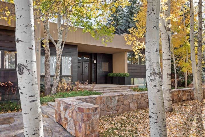 This thoughtfully designed home is nestled in one of Aspen's most exclusive enclaves. Designed with privacy, entertaining and gracious living in mind, enjoy the beautifully landscaped grounds that include a large outdoor patio, hot tub, manicured lawn, and mature gardens with a pond and waterfall - this home has it all. Greeted by an elegant foyer, you enter the vaulted ceiling living room with floor to ceiling windows. Comfortably utilize the seating areas, one centered around the double sided fireplace, and the other around a 72'' television screen.  A full wet bar is conveniently placed for drinks and snacks, with a table for cards or putting your puzzle together by the fire. This thoughtfully designed home is nestled in one of Aspen's most exclusive enclaves. Designed with privacy, entertaining and gracious living in mind, enjoy the beautifully landscaped grounds that include a large outdoor patio, hot tub, manicured lawn, and mature gardens with a pond and waterfall - this home has it all.  Greeted by an elegant foyer, enter the vaulted ceiling living room with floor to ceiling windows. Comfortably utilize the seating areas, one centered around the double sided fireplace, and the other around a 72'' television screen.  A full wet bar is conveniently placed for drinks and snacks, with a table for cards or putting your puzzle together by the fire.  The dining room is located on the opposite side of the double-sided fireplace, with 2 separate tables, one with seating for 10 and the other with seating for 4 or combine them for combined seating for 14.  The gourmet kitchen is a chef's delight, with ample workspace, a farmhouse kitchen sink, 2 prep sinks, a 6 burner Wolfe gas stove, double ovens, double warming drawer, and a subzero refrigerator and freezer.  There is a breakfast nook for 6.  5 of the bedrooms in this house offer an oxygen system that allows you stimulate the elevation of where you're from. Other features include a temperature-controlled wine cellar 