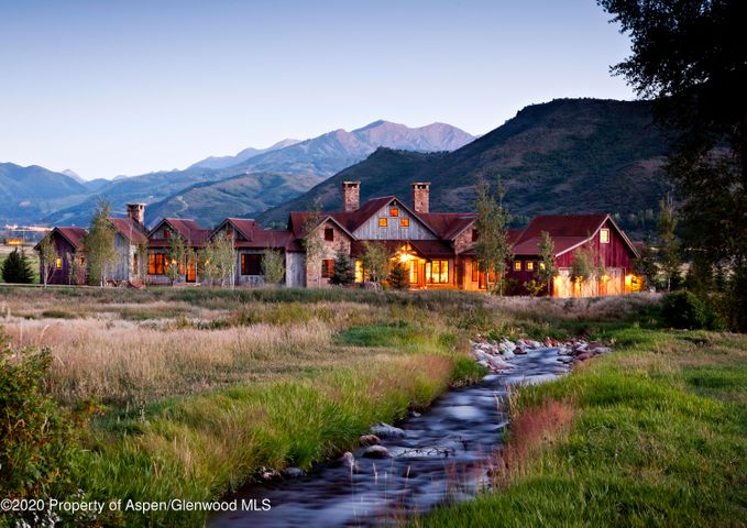 Aspen Valley Ranch is Aspen's only whole ownership private luxury serviced community. Situated on 800+ acres, homeowners enjoy luxury services, amenities and activities. Michael Fuller Architects elevated the ranch architectural vernacular with the 5,461 square foot Highlands House, a 4-bedroom, 4.5-bath residence that overlooks a tranquil scene of pasture and creek with views of Buttermilk, Aspen Highlands and Aspen Mountain. The single-story floorplan has been centered around a large great room, anchored by a beautiful stone floor to ceiling fireplace. Flanking the great room, a media room and morning room offer ideal breakout spaces for family. Vaulted ceilings and large picture windows in every room, timber, reclaimed woods, local Colorado stone and other rustic elements have been meticulously applied to each space. The large gourmet kitchen has a large center island, pantry, luxury appliances and convenient access to the patio for seamless al fresco entertaining. An open hall accommodates multiple dining tables with access to the outside. In one wing of the house, there is an office and master suite, warmed by a fireplace and enriched by a magnificent bath, spacious walk-in closet, light-filled windows and doors leading to a private patio.  In the opposite wing, there are two bedrooms plus guest master suite with a fireplace.