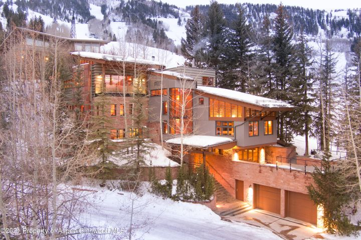 It has become in vogue in today's Aspen real estate market to refer to a listing as a legacy property, but for the House on Little Nell, ''heirloom'' is perhaps more apropos. Envision Aspen of the 1950's and what comprised the fledgling ski and mountain resort experience. Flash forward to today, and what has remained a constant throughout the changing character of the decades is the irreplaceable location and appeal of the House on Little Nell. Nestled against one of the world's most recognized ski trails and literally in the shadow of the Silver Queen gondola, the expression ''if these walls could talk'' is delivered with the wink of an eye as memories of the original home have been transformed into Aspen Mountain's transcendent ski-in/ski-out property. Today, the 7,150 square foot mountain contemporary home sits amongst mature aspen and pine trees overlooking downtown Aspen. A short walk down the hill is every amenity that has established Aspen as a year-round, world-famous destination. Situated on a 10,000+ square foot lot, the home features inviting and convenient outdoor spaces begging to entertain. The expansive main level deck directly off the slope and hidden from skiers and hikers offers outdoor dining and lounging in perfect privacy. A rejuvenating soak in the hot tub on the spacious lower-level deck serves up relaxation and views to the stars. Indoors, the four livable levels include a large great room with bird's eye views across Aspen, an adjacent open kitchen and sitting area, and a spacious east-facing master bedroom with views toward Indy Pass, his & her bathrooms, and walk-in closets. Three generous above grade bedroom suites, huge media and playroom with sunken floor, ski-in equipment room, large elevator, and strategically placed powder rooms all allow for plenty of room to claim your space in a once in two generations opportunity to own a slope side home with one of the richest histories of any property in Aspen.