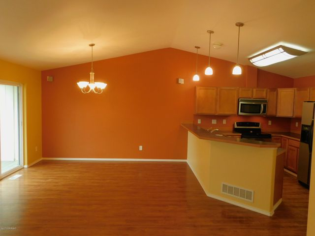 Kitchen and adjacent dining offers accent wall and clean lines.