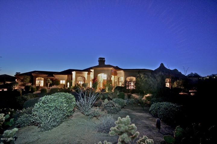 Serenity on nearly one acre of easy care desert landscape with sparkling city lights mountain views and Sonoran Sunsets