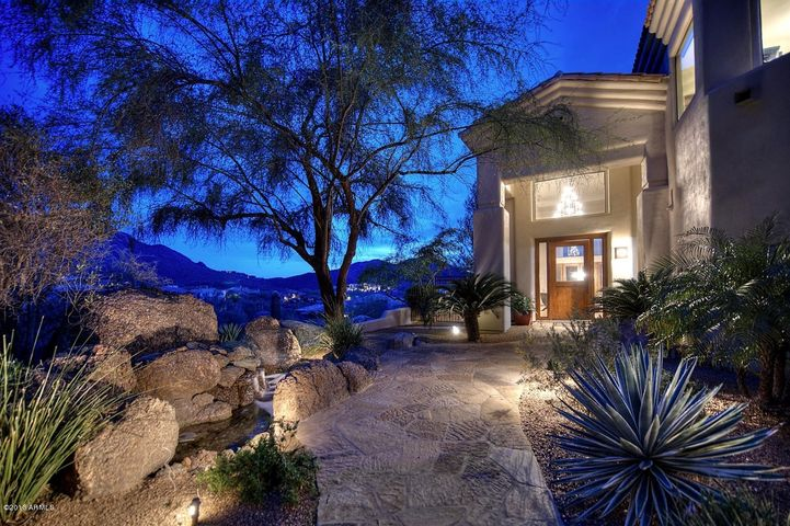 City light and mountain views await you along the flagstone and boulder entry of this desert oasis in Quail Ridge at Troon.