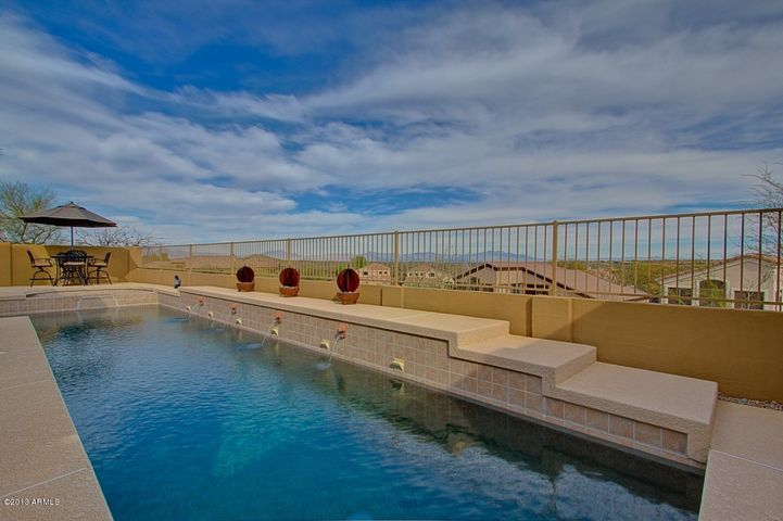 This pool is self cleaning, heated, pebbletec lap pool with side handles for exercising and water feature. Forever Mountain Views, much better than the pictures. Large Buffer behind home. Outdoor BBQ, Misting System. Cool Decking.