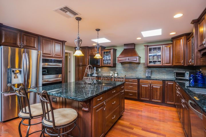 Custom cherry wood cabinets, stainless appliances and slab granite counters