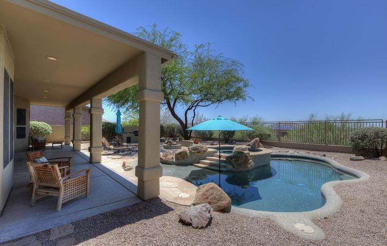 Private lot with natural space behind is the perfect backdrop for this resort like backyard complete with pool, spa, gas firepit and built-in BBQ.