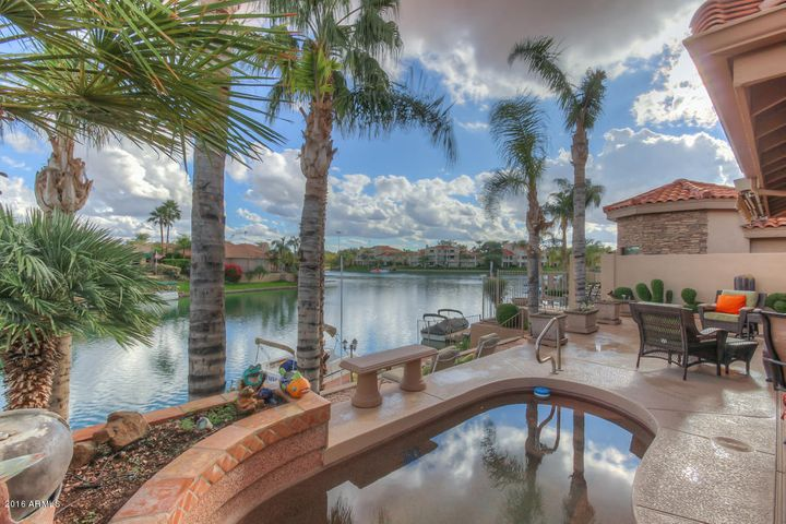Waterfront lot with a spool, boat dock and several patio areas.