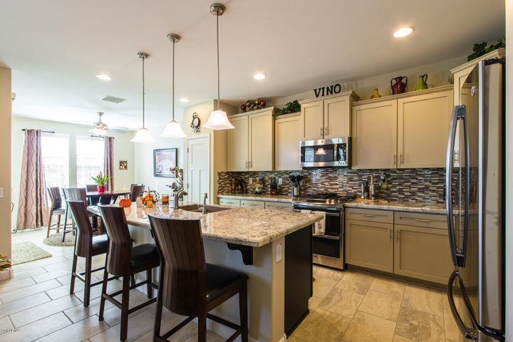 Gourmet kitchen with granite slab counter tops, double ovens, gas cook top, and beautiful tiled backsplash.