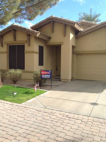 Front of home with desert landscaping and grass