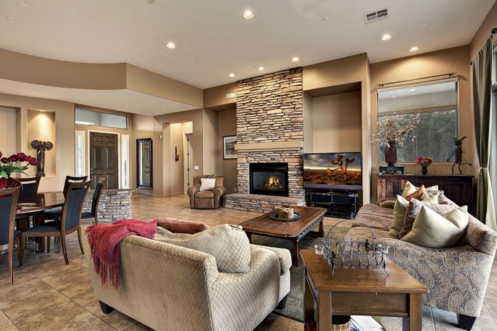 Great room is anchored by a stacked stone fireplace and opens to the formal and casual dining areas for easy entertaining.