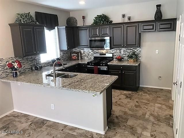 Open kitchen with new granite slab c-tops, Stainless steel under mount sink, Gas range brushed nickel faucet, tile backsplash and custom painted cabinets.
