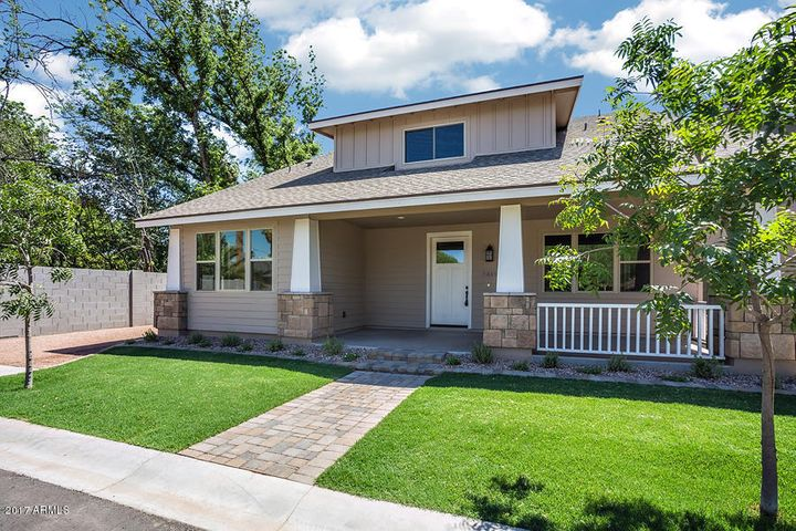 Craftsman style home features inviting front porch and stone clad columns.