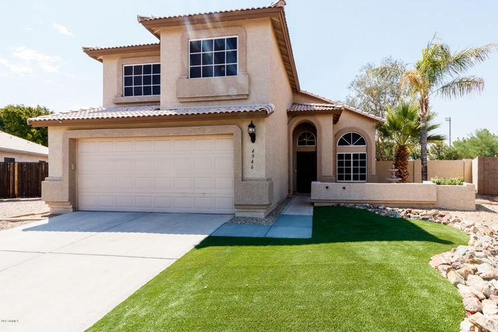 View From the corner featuring the synthetic grass, front paver patio, and flower bed.