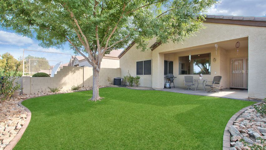 Luscious green back yard with patio, and views of golf course