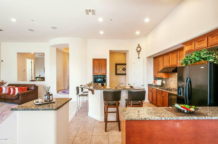 Highlights of the gourmet eat-in kitchen includes full walk-in pantry, gas cooktop, granite counter tops, and striking black appliances.