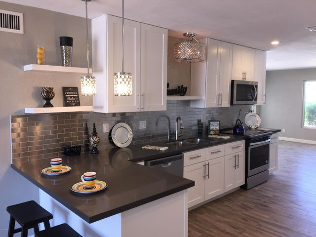 Upgraded Shaker cabinets with trendy hardware, quartz counters, breakfast bar and elegant light fixtures