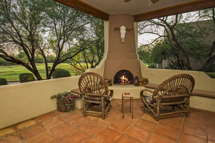 Cozy fireplace is enjoyed in large covered patio that wraps around to the side of the house.