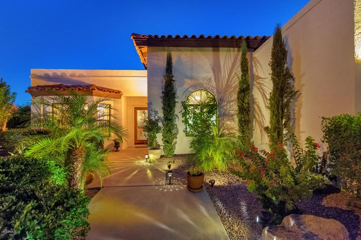 Front of home with beautiful landscaping and outdoor lighting