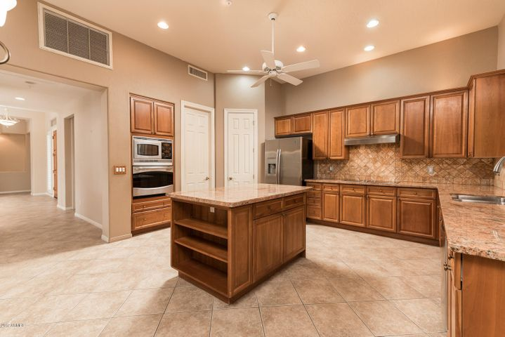 Kitchen features stainless appliances, granite counters, tile flooring , and island for added counter space and storage.