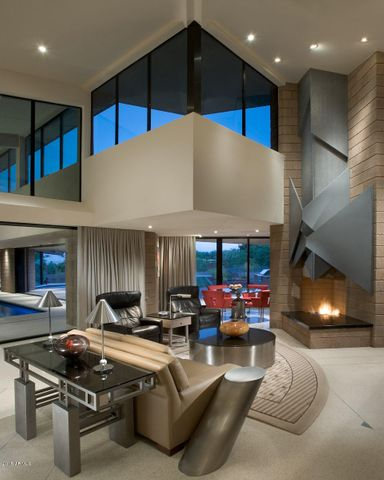 One of a kind fireplace with dark granite hearth & 4 brushed glass triangles that fold over the chimney accentuating the fireplace as a focal point