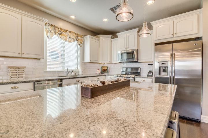 This kitchen has it all! Upgraded, staggered, white cabinetry with crown molding detail. Whirlpool stainless steel appliances including an upgraded gas stove & dual ovens. Huge kitchen island with breakfast bar and upgraded pendant lighting.