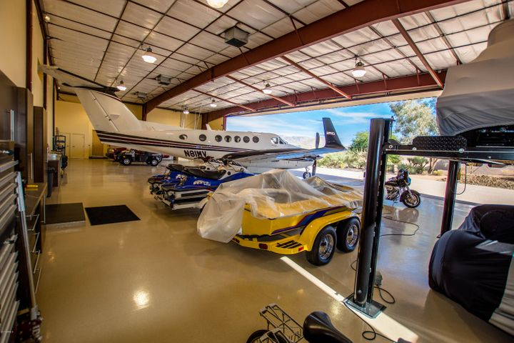 The ultimate toy barn. Look at the number of planes, cars, boats, motorcycles that the hangar accomodates. Four big air exhaust fans, and RV hookups as well.
