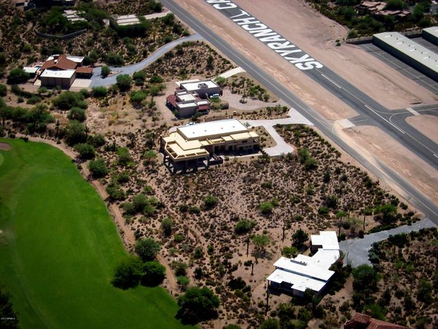 Aerial view of the home, sandwiched between the runway and Desert Forest Golf Course, where memberships are available. There's a lot next to this home, also available. Ask us for more details.