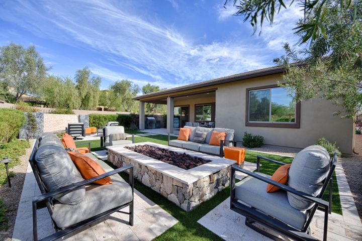 Enjoy this custom designed, resort style backyard. A fire pit, fountain with fire pit, synthetic grass, mature landscaping and so much more create ambiance of a 5Star Resort.