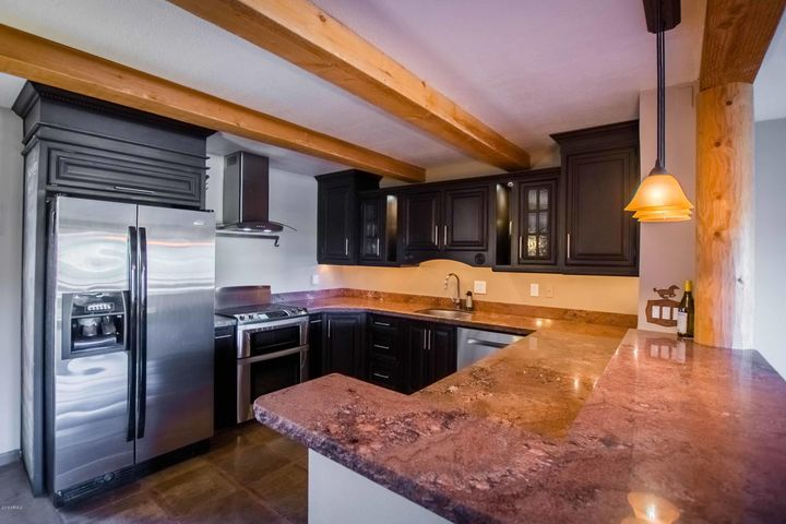 Large granite counters with a breakfast bar, and cherry cabinets.