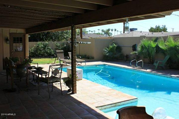 The backyard features an extended patio, spacious swimming pool, and room to garden.