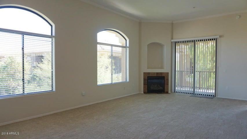 Bright living room overlooks a greenbelt.