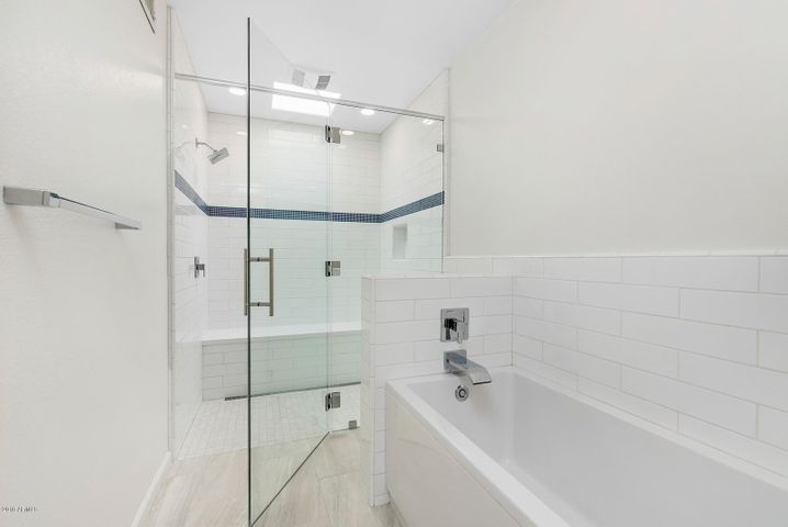 Redesigned with a zero grade entry to an over-sized walk-in shower with subway tile and a built-in bench. In addition, there is a new soaking tub with subway tile accent wall.
