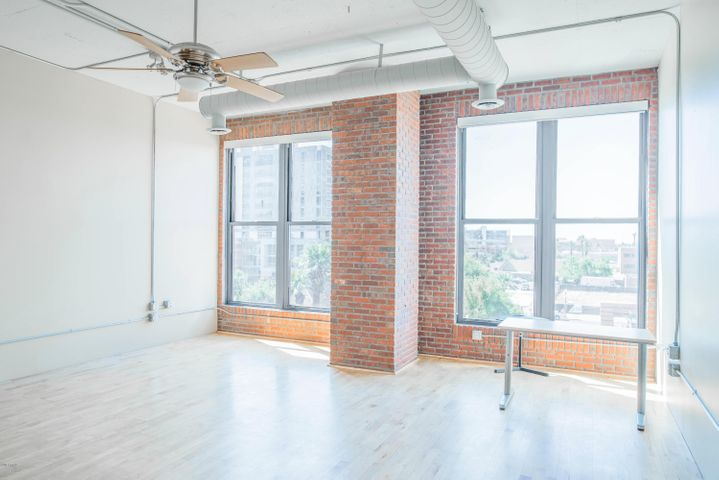 Loft style living room with large windows, exposed brick and hardwood floors