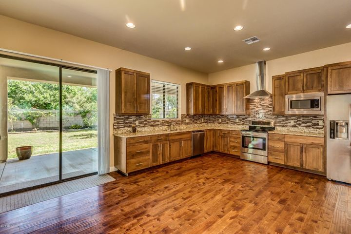 """Kitchen features 42"""" cabinets, stainless steel appliances and granite countertops."""
