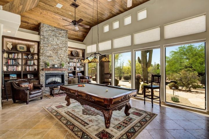 The great room features a floor to ceiling electric fireplace, built-in bookshelves, tongue and groove wood ceiling and lots of windows for taking in the views.