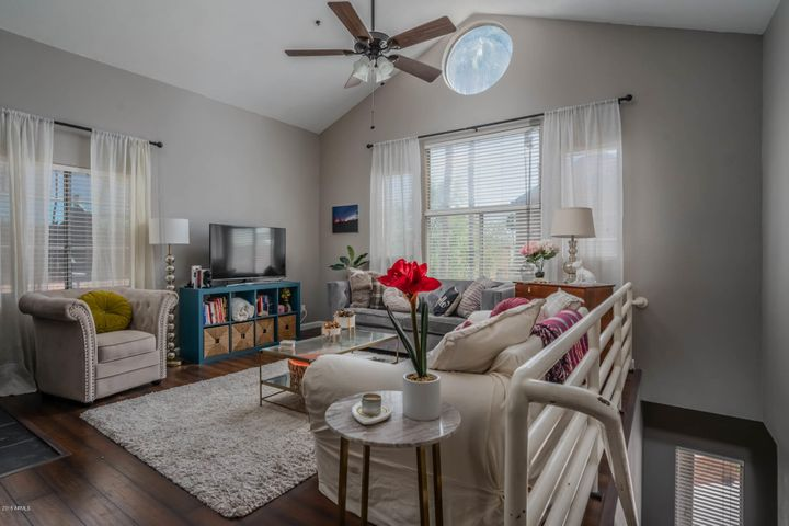 The living space is open and bright, with large windows and a vaulted ceiling!