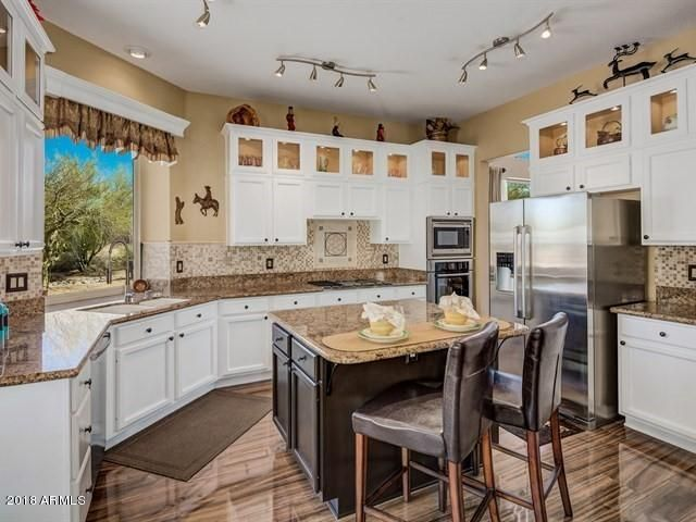 The chef's kitchen has been upgraded with stainless appliances, white cabinetry, stone backsplash and island that has seating with additional cabinetry and storage.