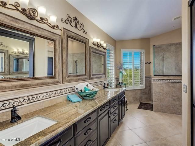 The luxurious master bath was recently updated with granite counters, travertine flooring, large walk-in with stone surrounds, and beautiful trim.