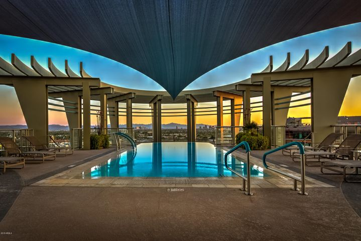 Resort style roof top negative pool and spa area at sunset
