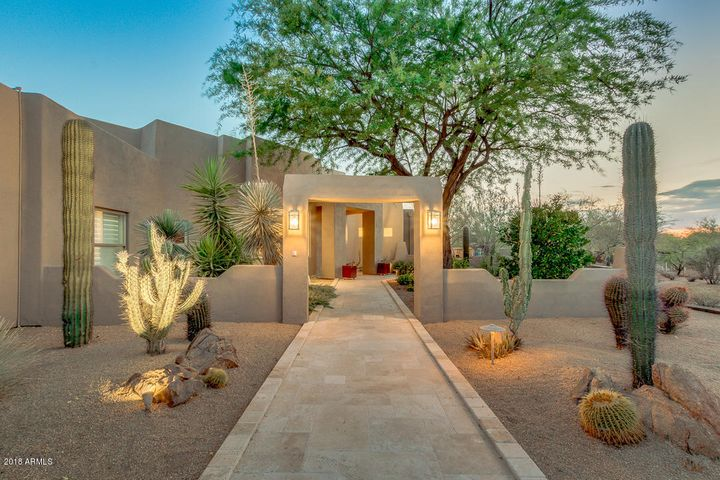 Inviting front entry with travertine pavers and contemporary lighting