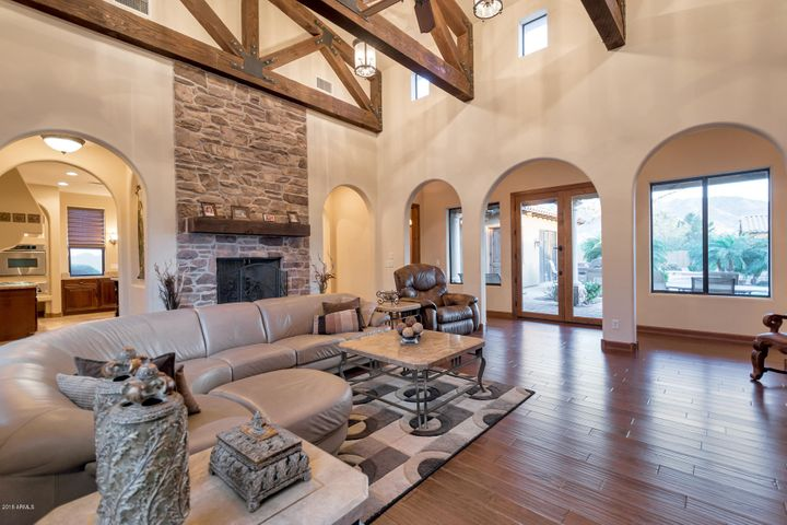 Grand cathedral vaulted family room with stone fireplace