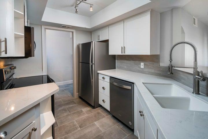 glazed brick backsplash, quartz Carrara counter, Stainless steel Whirlpool Appliances, New hardware, New shaker cabinets. New Sink.
