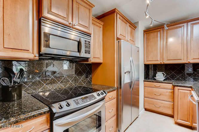 Expanded, remodeled kitchen with stainless appliances and granite countertops and backsplashes.