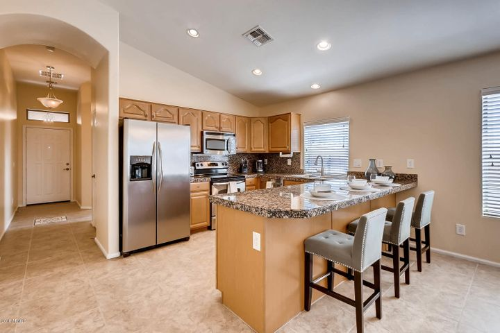 Well appointed kitchen with granite, stainless steel appliances, and spacious island to enjoy breakfast