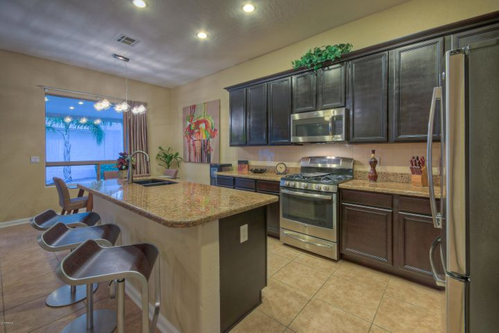Kitchen boasts granite counter tops & sink, GE Profile stainless steel appliances and breakfast bar.