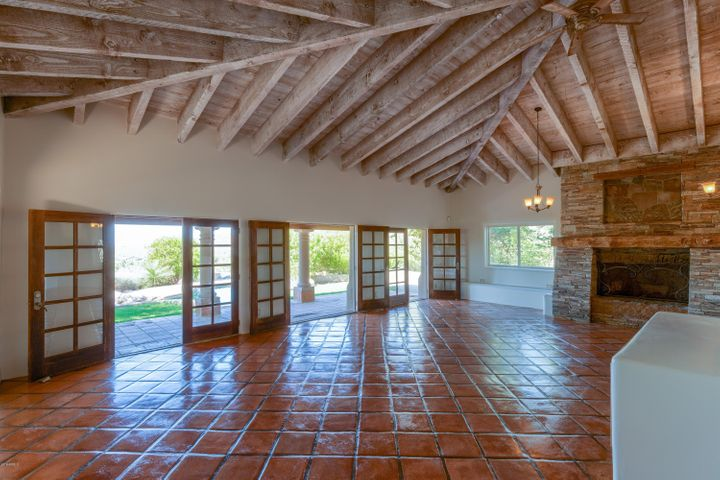 Spanish influence adorns this great room with huge stone fireplace and tongue-and-groove soaring ceiling.